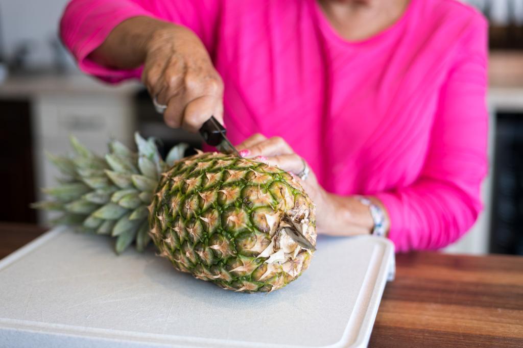 Cutting the pineapple in half.