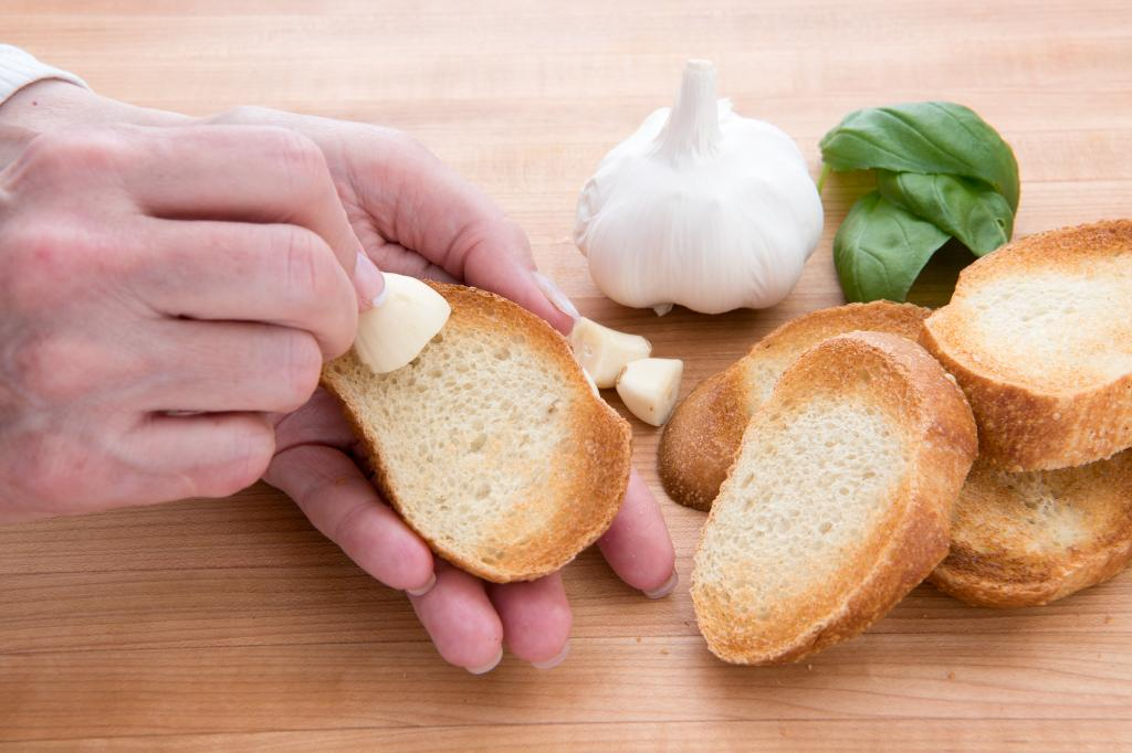 Rubbing the bread with garlic.