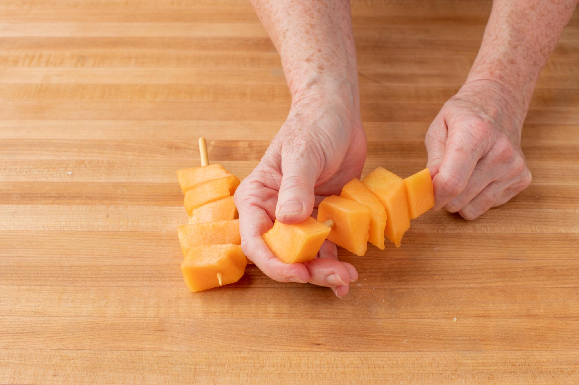 Placing the cantaloupe on the skewers.