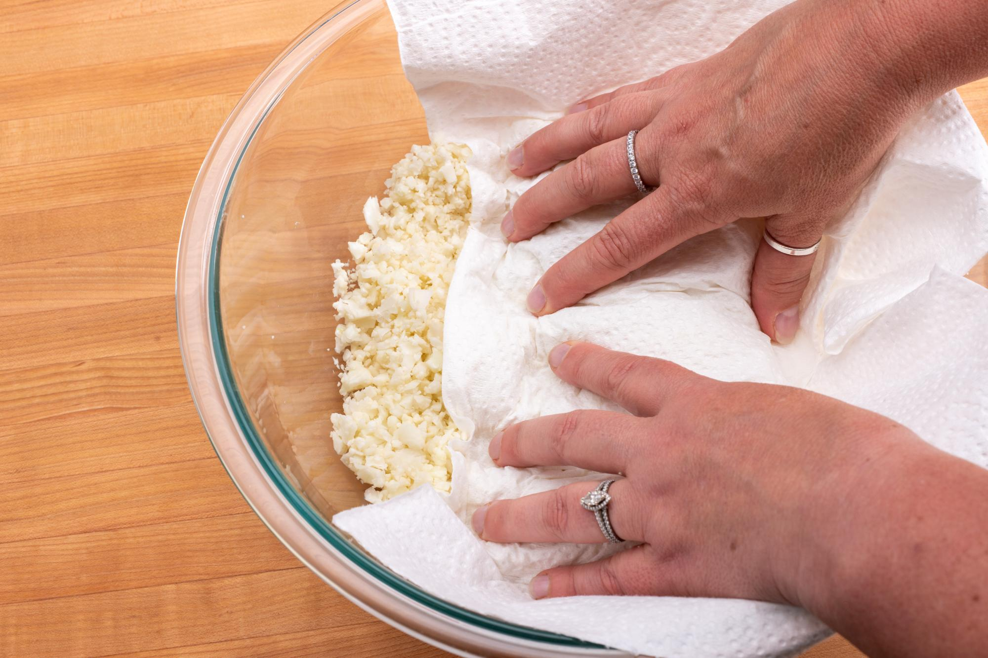 Patting dry the riced cauliflower.