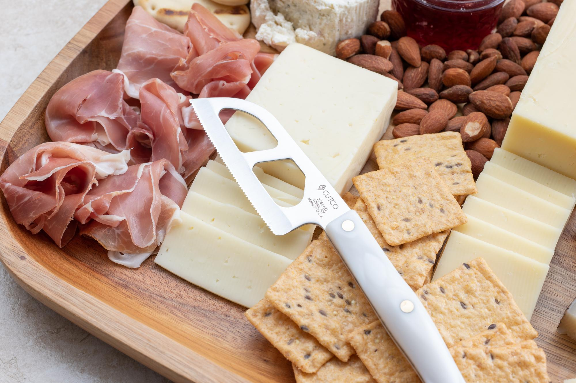 Santoku Style Cheese knife on the board.