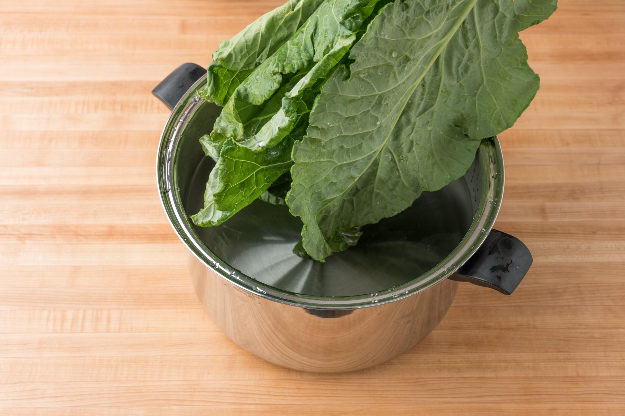 Submerging the collard greens in cold water.