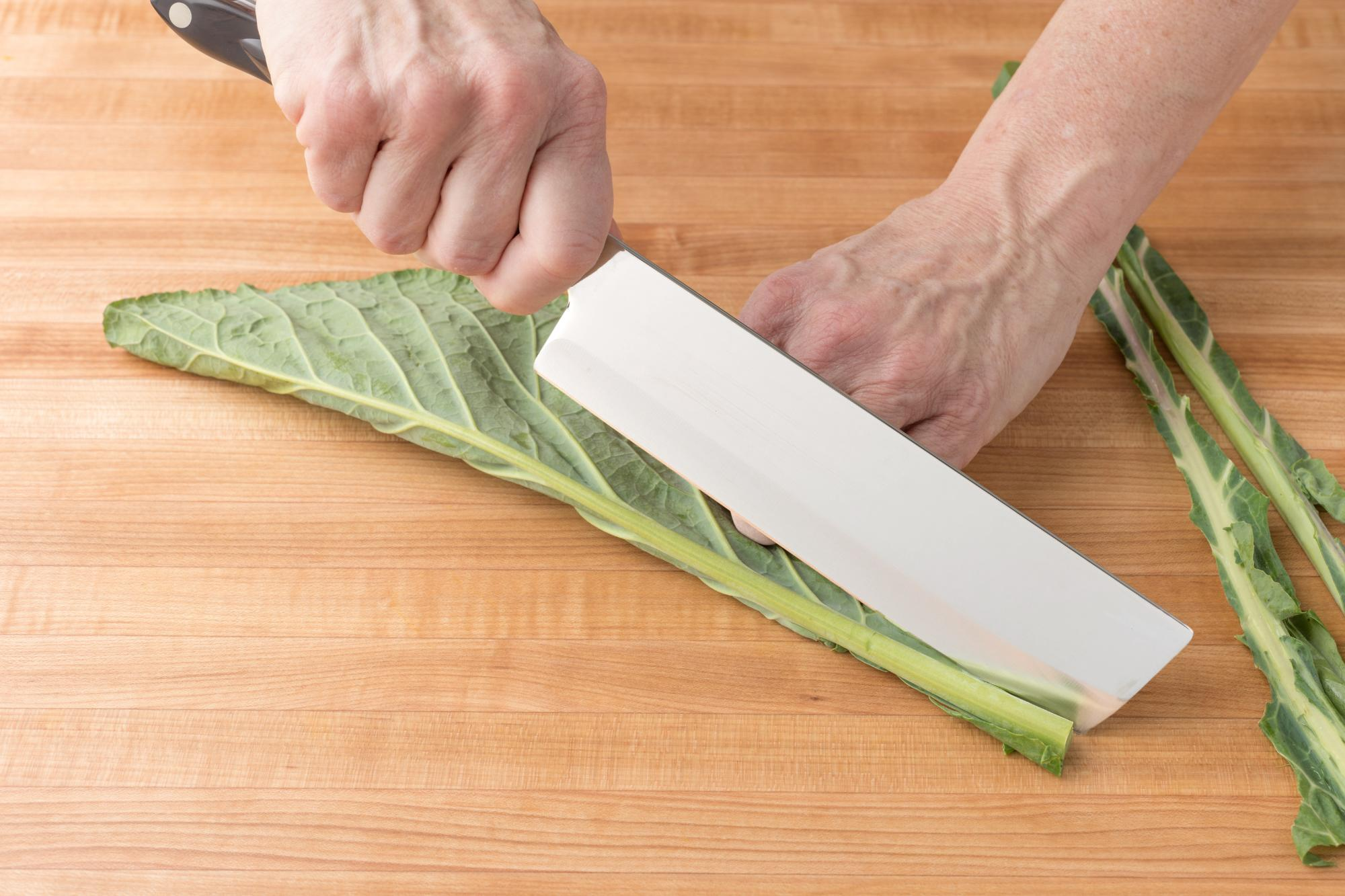 Slicing the stem of the collard greens with a Vegetable Knife.