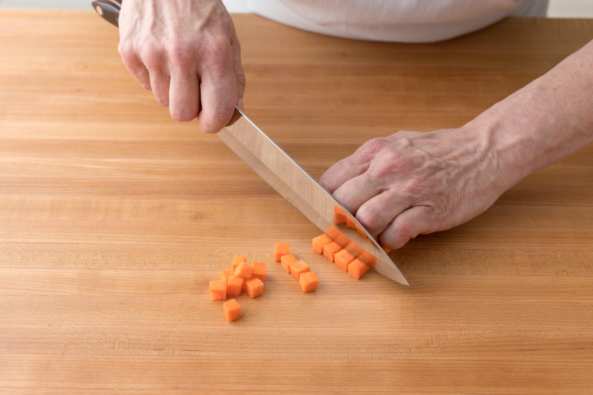 A Petite Chef being used to dice carrots.