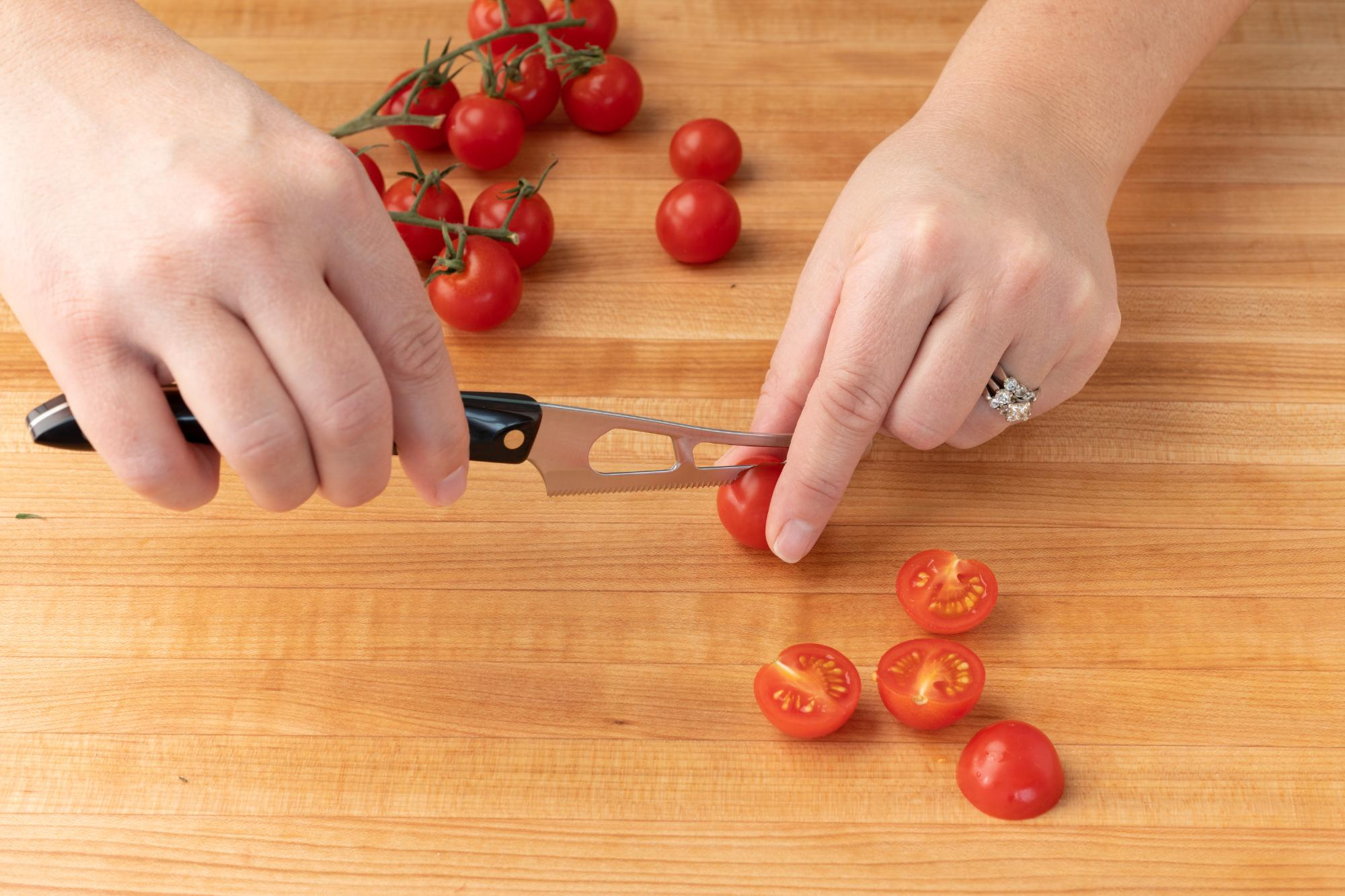 Using the Mini Cheese Knife to slice the tomatoes in half.