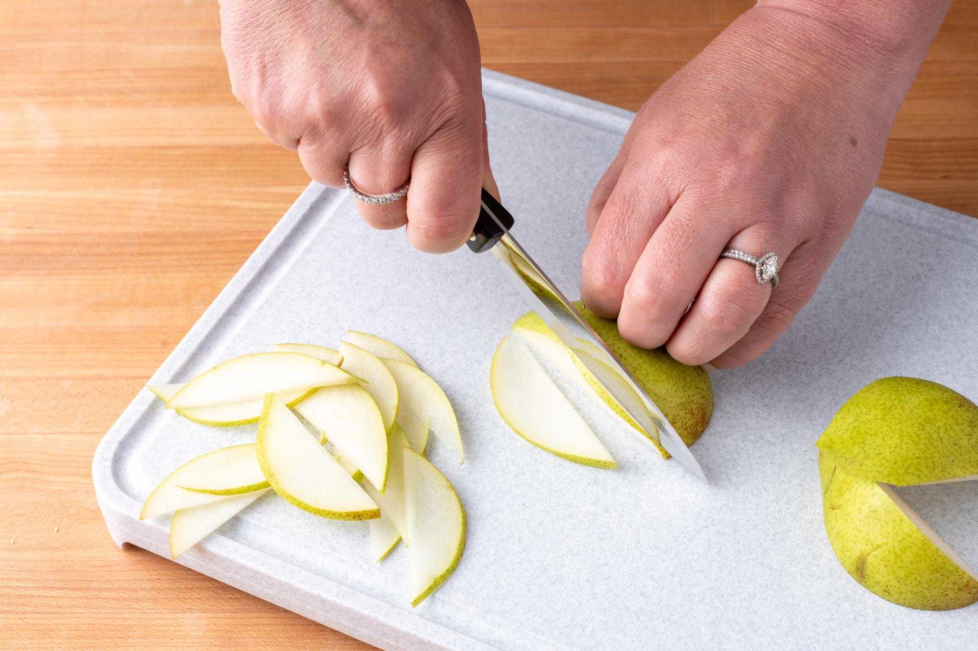 Using the 4 inch Paring knife to slice the pear.