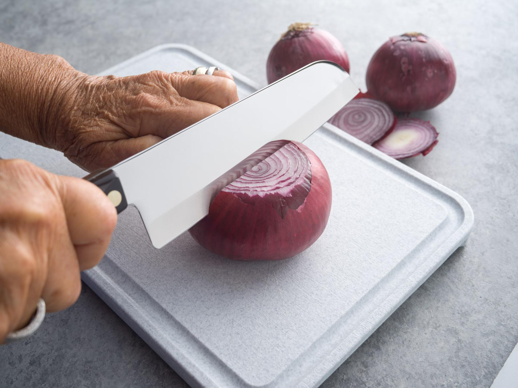 Cutting red onion with a Santoku.