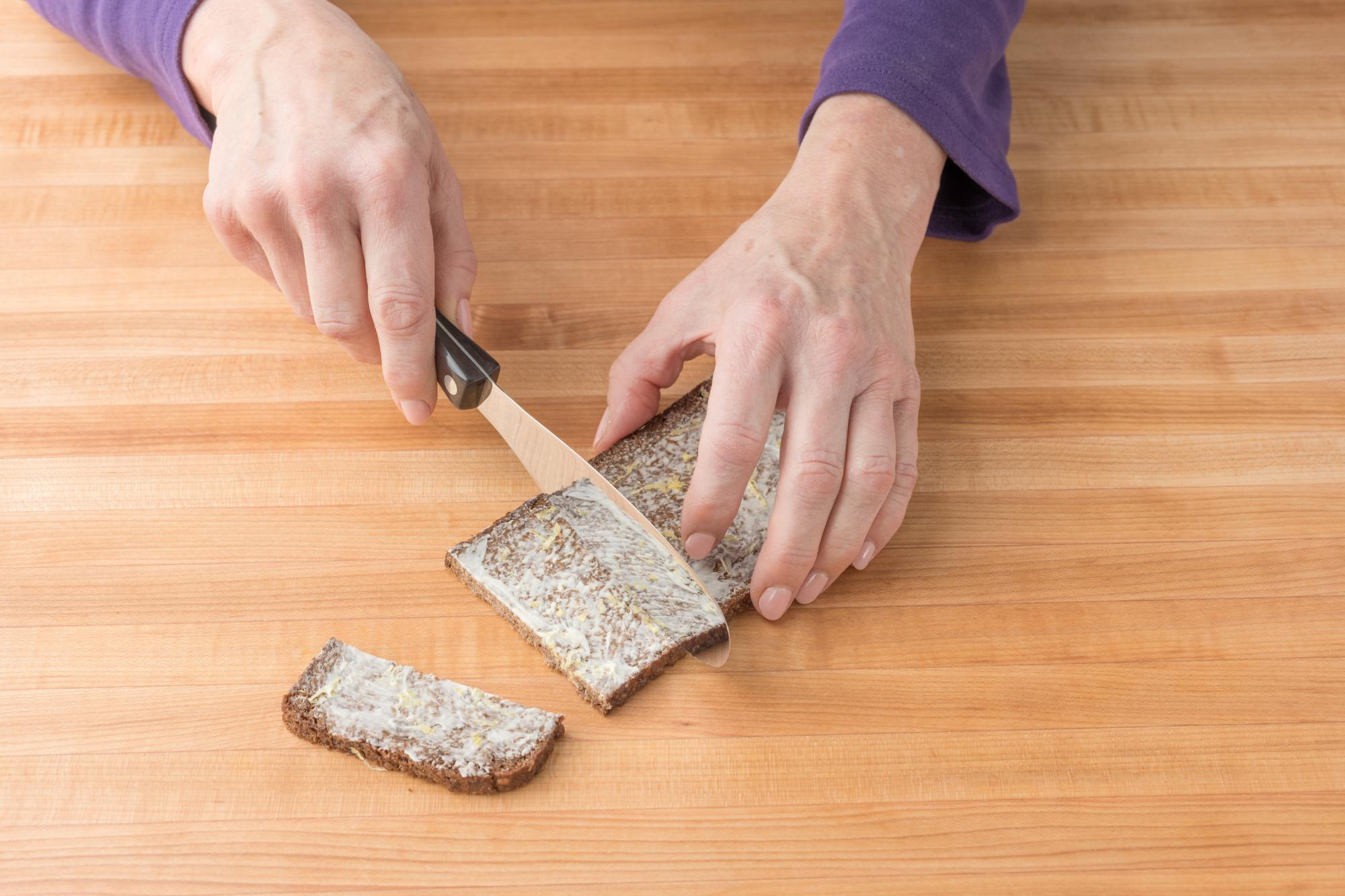 Using a Spatula spreader to cut the bread into appropriately sized slices