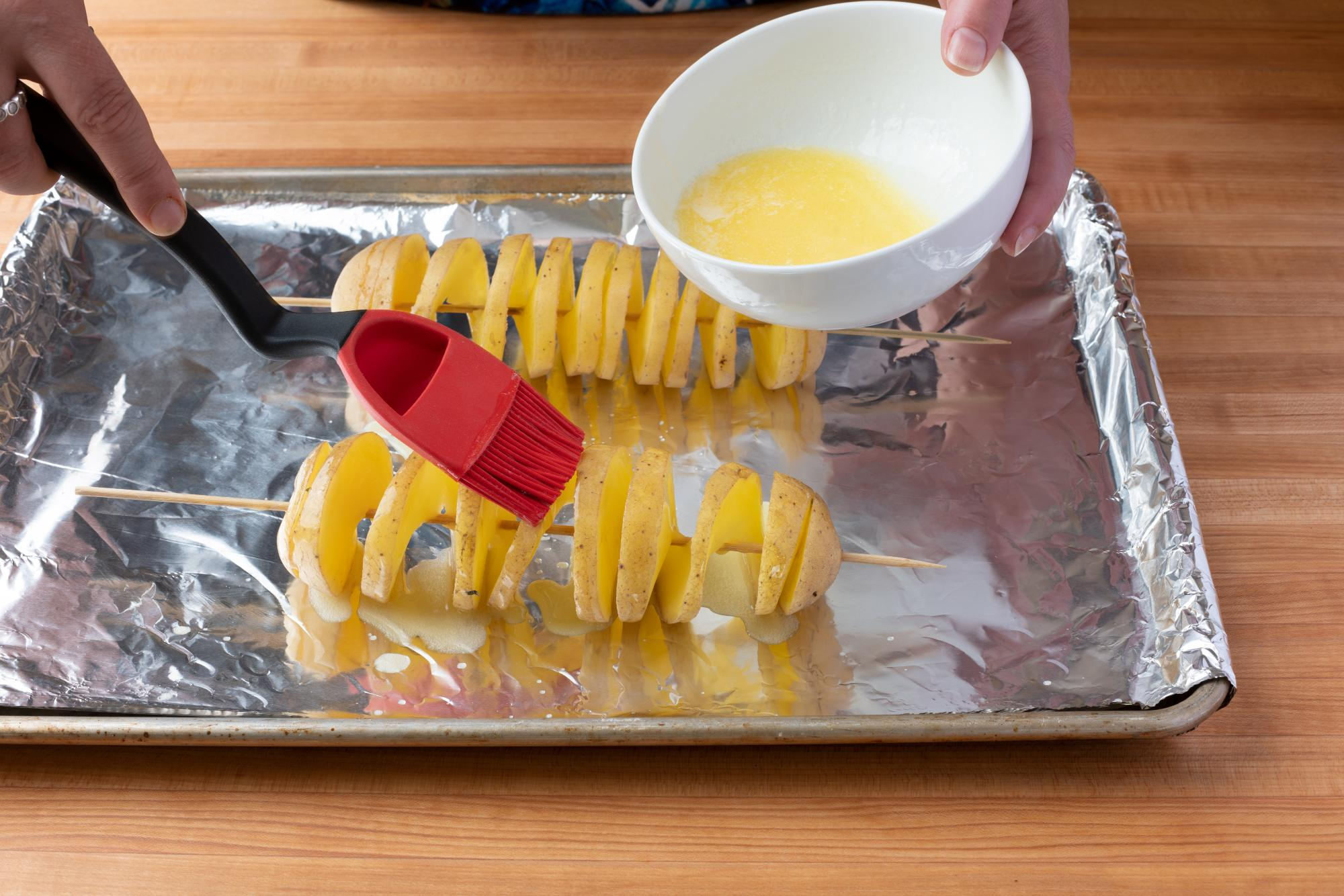 Brushing the potato with butter.