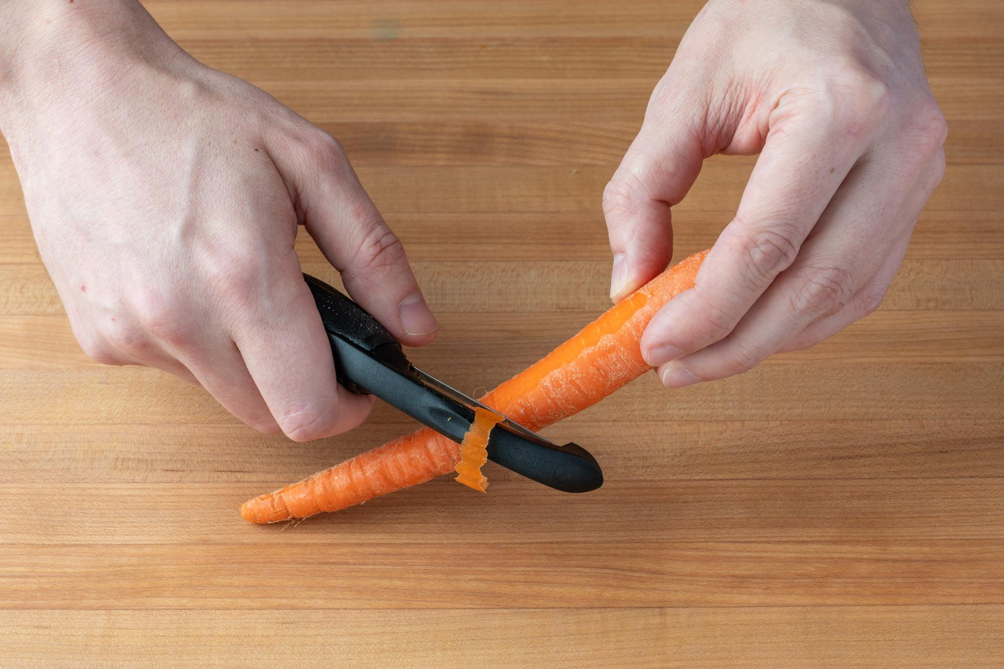 Peeling the carrot with a Vegetable Peeler.