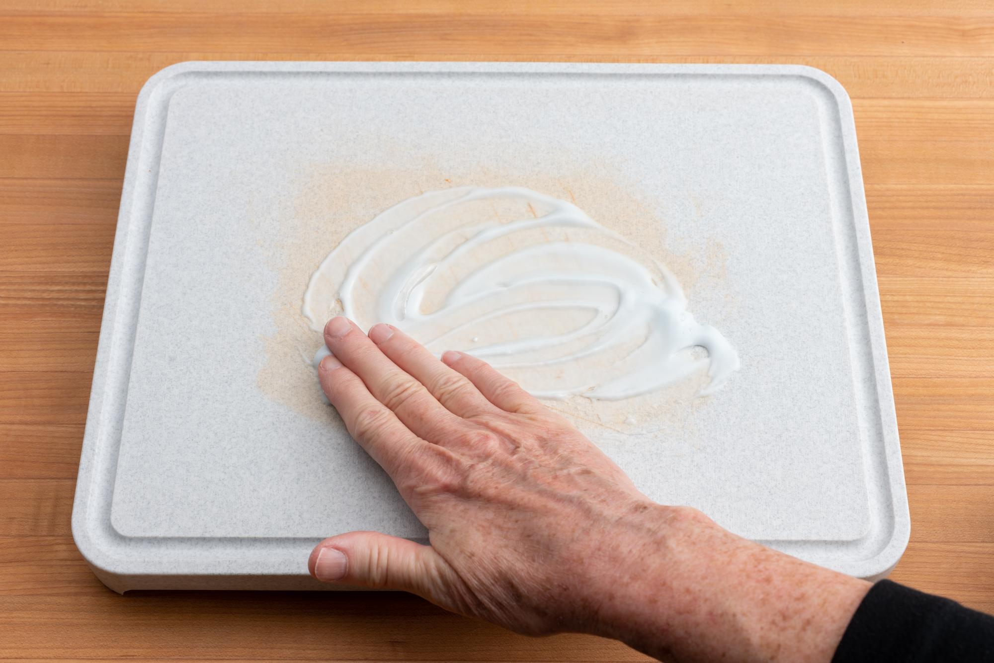 Rubbing the paste onto the board.