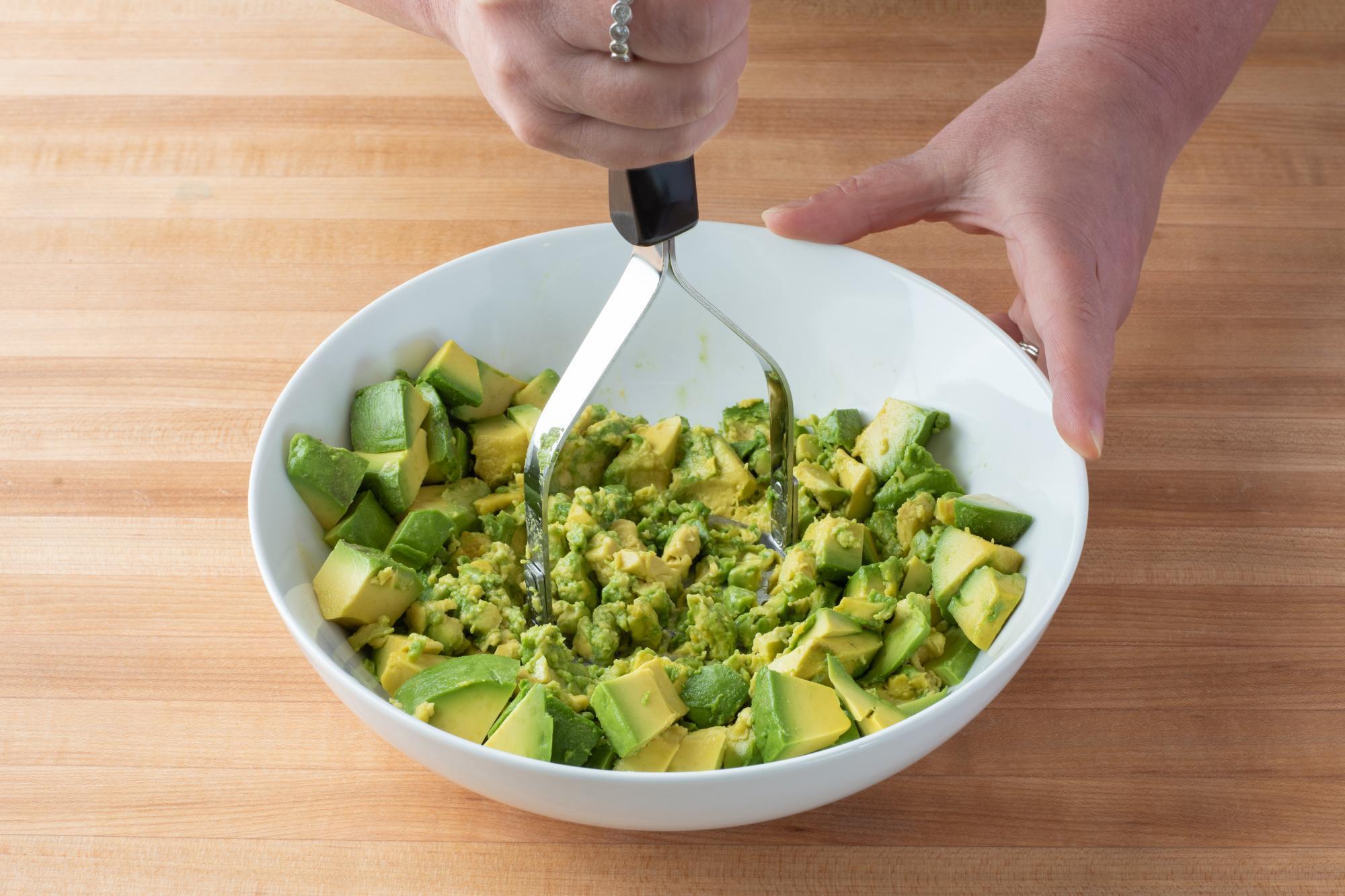 Mashing the avocado with the Potato Masher.