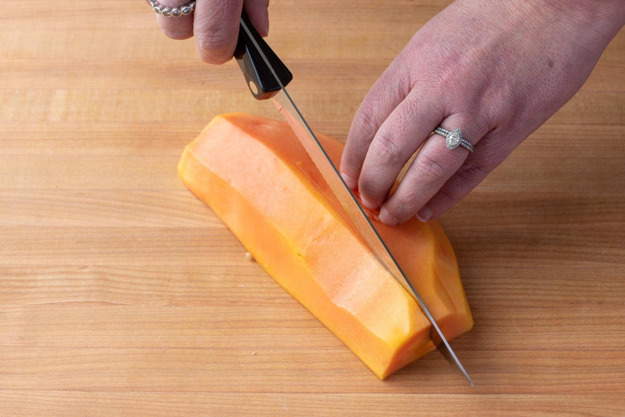 Cutting the papaya into quarters with the Petite Carver.