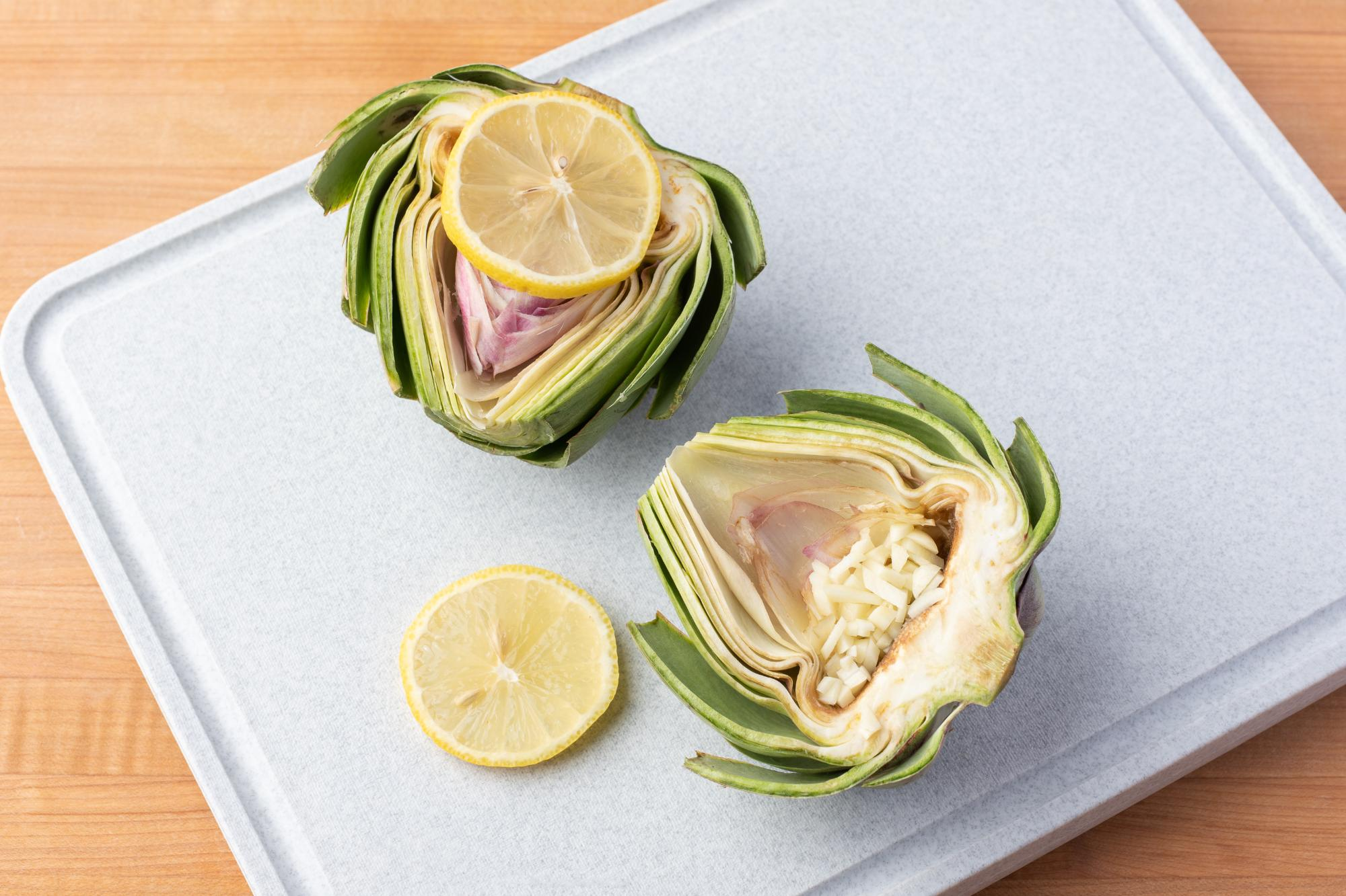 Filling the artichoke with garlic and covering it with a lemon slice