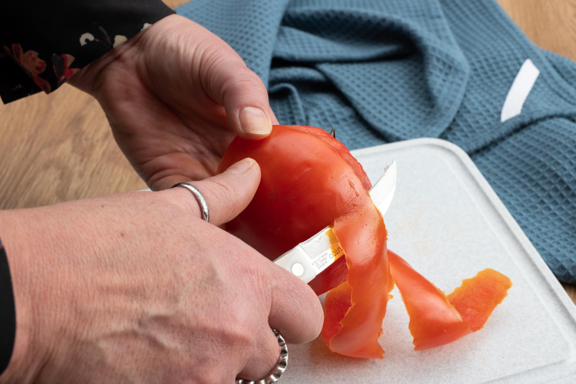 Continuing to peel the tomato.