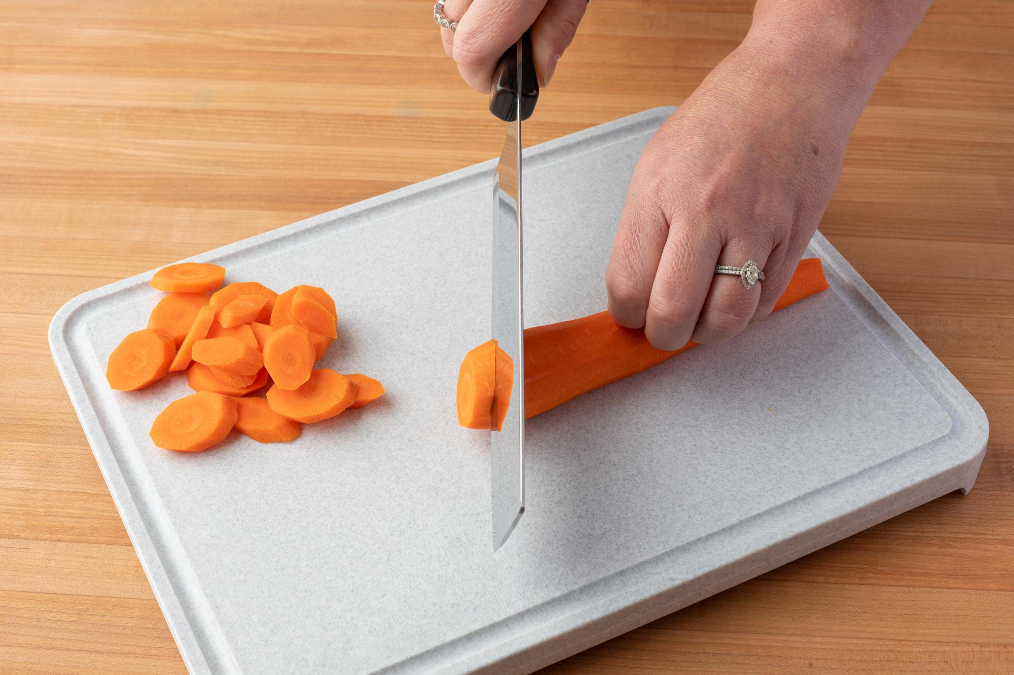 Cutting the carrot on the bias with a Vegetable Knife.