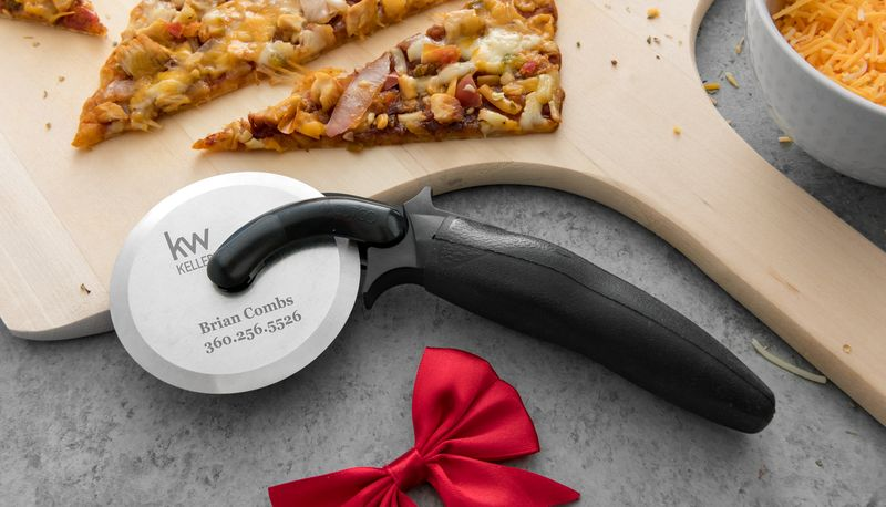 Closeup of Pizza Cutter in a home environment with business details engraved on metal.