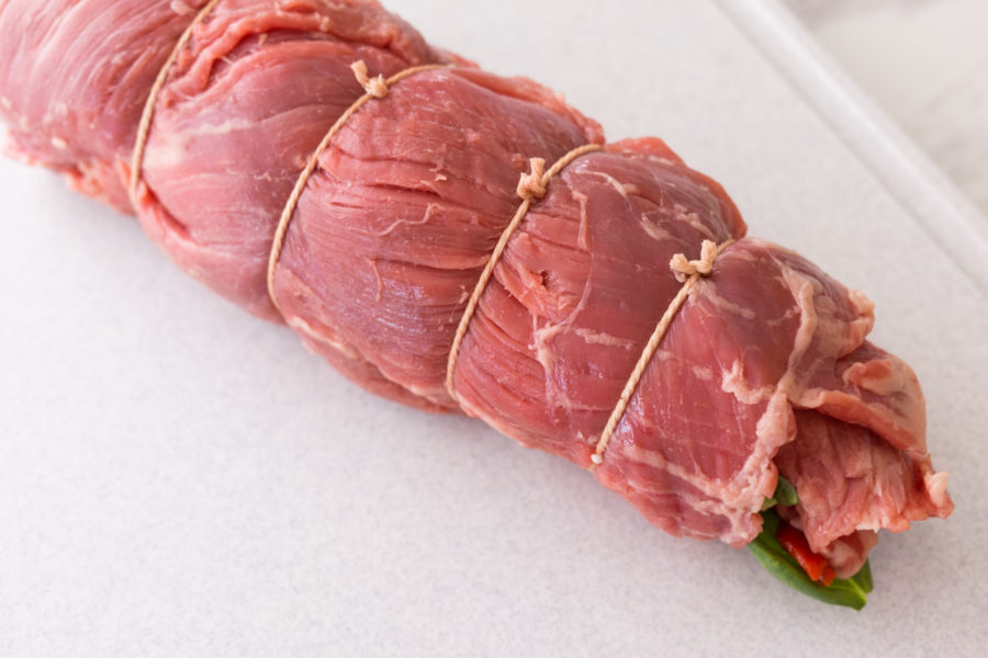 Rolled up flank steak stuffed with ingredients.